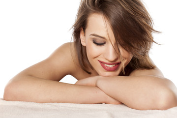happy young woman lying on her hands on a white background
