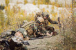 Постер, плакат: Soldiers team medic assists wounded taliban soldier