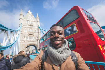 Man taking selfie in London with Tower Bridge on background