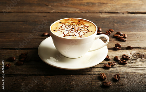 Foto op Aluminium Cafe Cup of latte art coffee with grains on wooden background