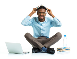 Happy african american college student sitting with laptop and b