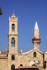 Orthodox church bell tower next to the mosque minaret, Cyprus