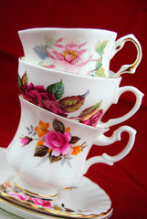 antiques cup and saucer with flower decoration on red background