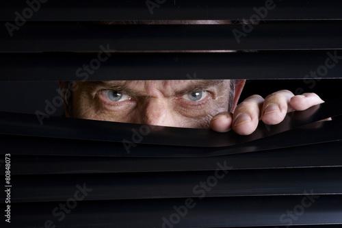 Man spying on something through venetian blinds - 80848073