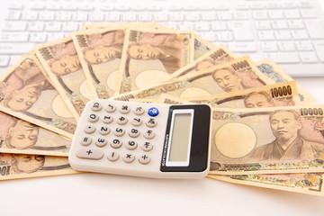 紙幣と電卓とパソコン