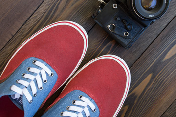 old camera and red shoes on a wooden table