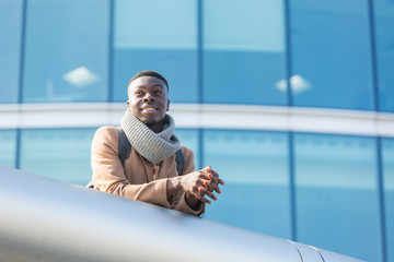Young black man in London with modern building on background.