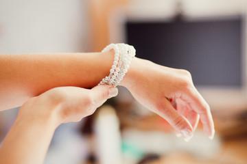 Bridal preparation, bride putting on jewelry