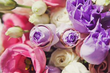 Wedding rings on a bouquet of pink flowers