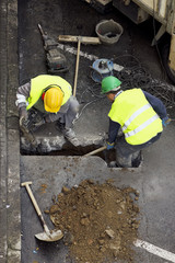 street workers repairing sidewalks and pipelines