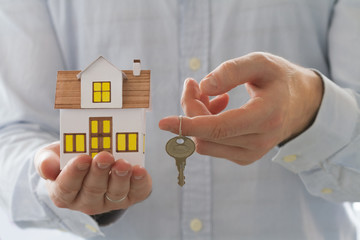 Mortgage concept. Businessman holding toy house and key in hand