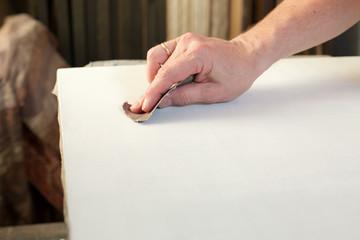 An artist priming canvas