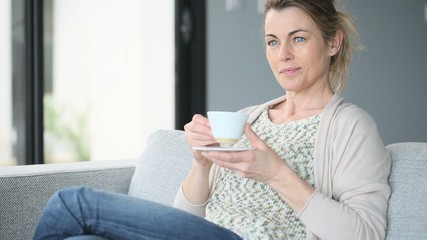 Middle-aged woman drinking coffee in sofa