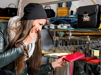 Beautiful young woman choosing leather purse