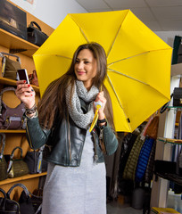 Young woman with yellow umbrella taking selfie