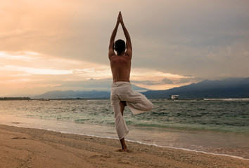 Man doing yoga on the sand beach with sunset