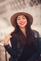 positive portrait of a stylish girl with a smile in a hat