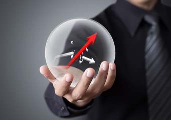 Businessman holds crystal ball with rising and broken graph