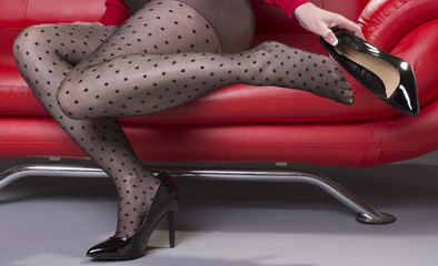 Woman sitting on a red sofa putting high heel shoes on