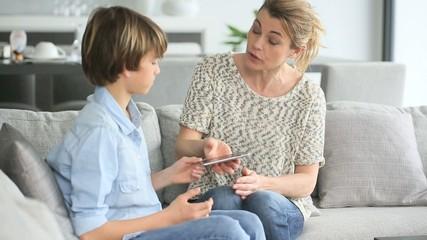 Mother giving warning to young boy using smartphone