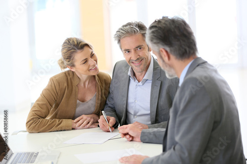 Mature couple signing financial contract at the bank - 80858668