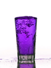 Glass of splashing Purple lemonade isolated on white background