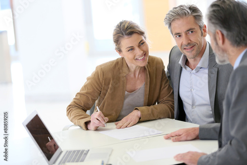 Mature couple signing financial contract at the bank - 80859215