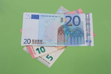 Euro notes on a plain green background.