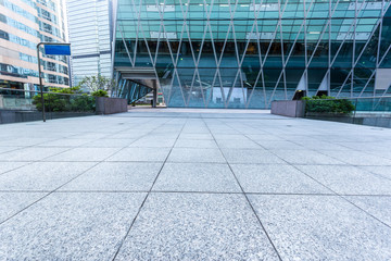 Empty pavement by the side of office building
