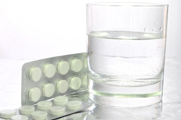 Glass with water and medicine, drugs, pills