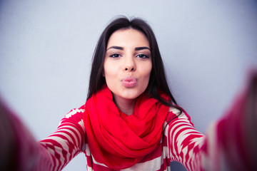 Beautiful woman kissing at camera over gray background