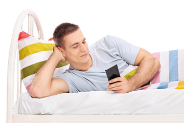 Man lying in bed and surfing on his cell phone
