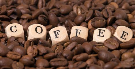 Kaffeebohnen mit Holzwürfel und dem Wort Coffee