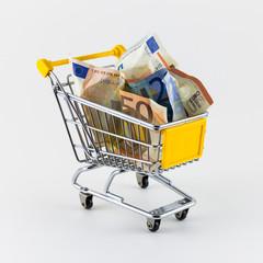 Einkaufswagen mit Geldscheinen vor weißem Hintergrund