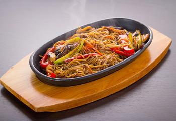 Soba noodles with meal and vegetables over black background
