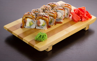 Sushi roll with eel on a gete over black background