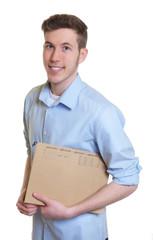 Lachender junger Mann mit blauem Hemd und Akte
