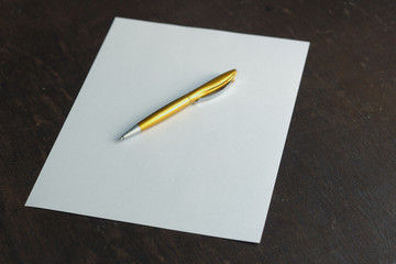 sheet of paper and golden pen
