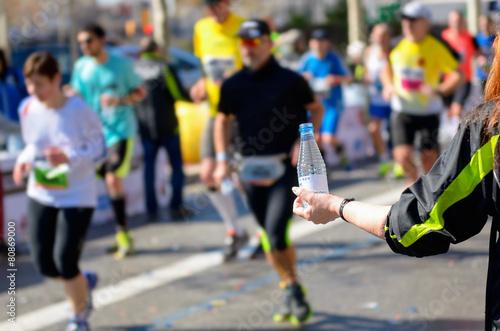 Marathon running race, runners on road, volunteer giving water - 80869000