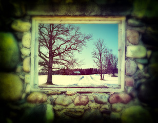 Winter landscape seen through window of old building