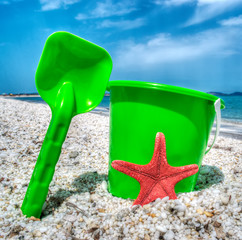 green bucket and spade by the sea in hdr