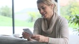 Mature woman at home using smartphone