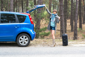 Young woman with a suitcase is hitchhiking on a forest road