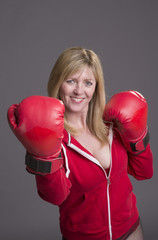 Blond female boxer with red gloves and jacket