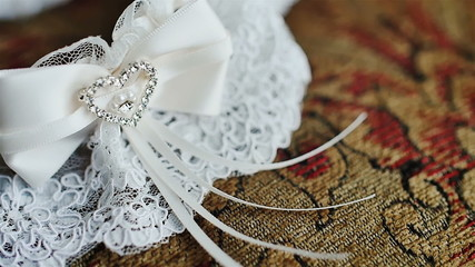 The garter of the bride laying on a pillow and prepared for wedd