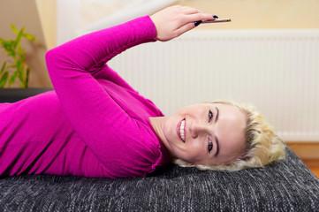 Junge Frau liegt auf der Couch mit Smartphone