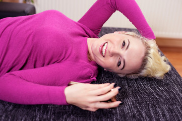 Junge Frau auf der Couch freut sich über Kurznachricht