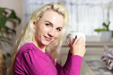 Junge blonde Frau mit Kaffeetasse