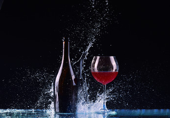 bottle and glass with red wine, water splash