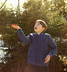 preteen handsome boy toss a coin on the country spring sunny vil